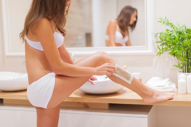 Foco mulher depilando perna no banheiro