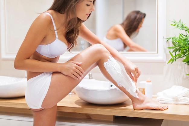Foco mulher depilando pernas no banheiro