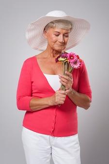 Foco mulher sênior cheirando flores frescas