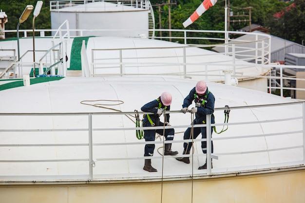 Foco na inspeção de segurança de altura de acesso por corda de trabalhador masculino do tanque de óleo e gás de armazenamento de espessura