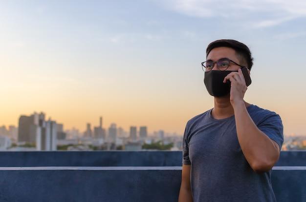 Foco parcial de homem asiático usando máscara facial para se proteger de vírus e fazer uma ligação.