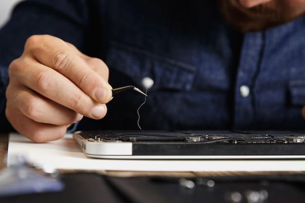 Foco próximo em pinças esd angulares com cabelos longos removidos do refrigerador quebrado do dispositivo eletrônico no centro de serviço