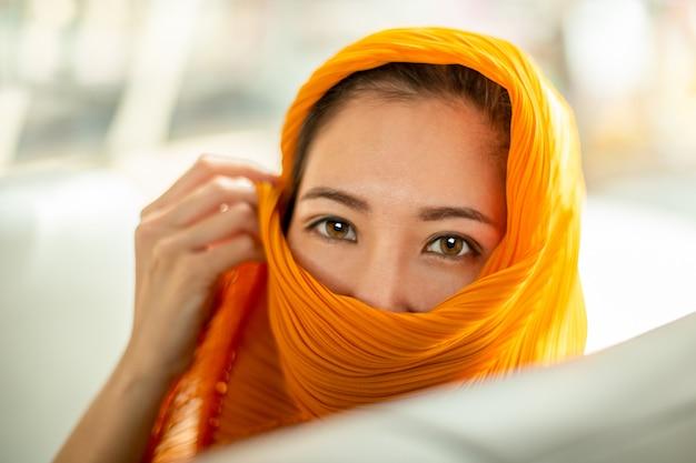 Foco selecionado bela mulher árabe olhos castanhos em hijab olhando para a câmera