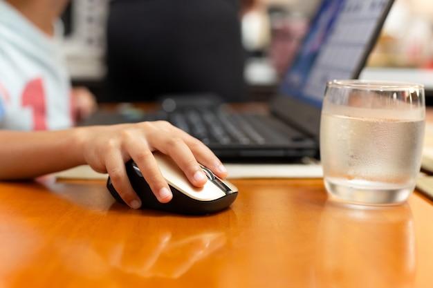 Foco selecionado childrens mão usando o mouse de computador portátil