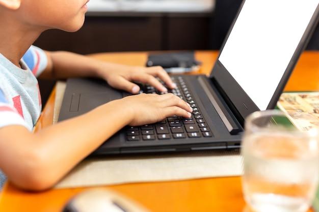 Foco selecionado childrens mão usando o teclado do laptop que joga o jogo