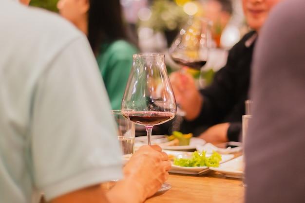 Foco selecionado de taças de vinho tinto na mesa no jantar de reunião no interior
