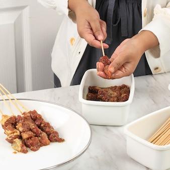 Foco selecionado na preparação do sabado caseiro de cordeiro (sate kambing) para o menu idul adha. sate kambing é comida de rua popular na indonésia. conceito de cozinha limpa