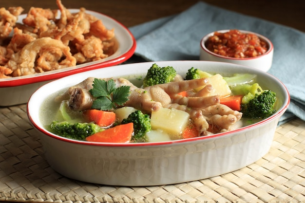 Foco selecionado pés de frango (ceker) em sopa de vegetais claros com batata, brócolis e cenoura. servido em mesa de madeira em tigela oval com sambal. e espaço de cópia de cogumelo de ostra para texto