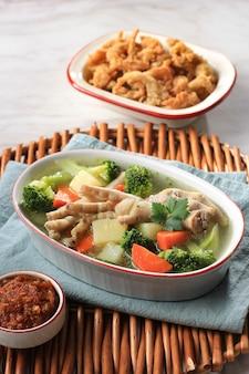 Foco selecionado pés de frango (ceker) em sopa de vegetais claros com batata, brócolis e cenoura. servido na mesa branca em tigela marrom com sambal e cogumelo ostra crocante.