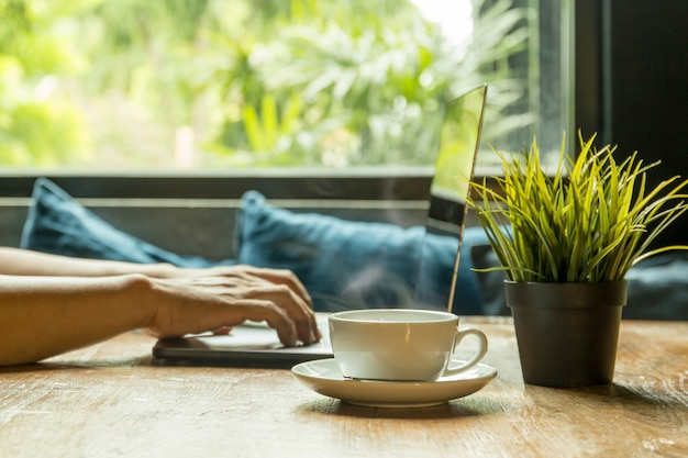 Foco selecionado xícara de café com empresário digitando no laptop teclado