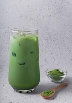 Foco seletivo, bebida natural matcha com gelo, latte com leite. chá em um copo alto