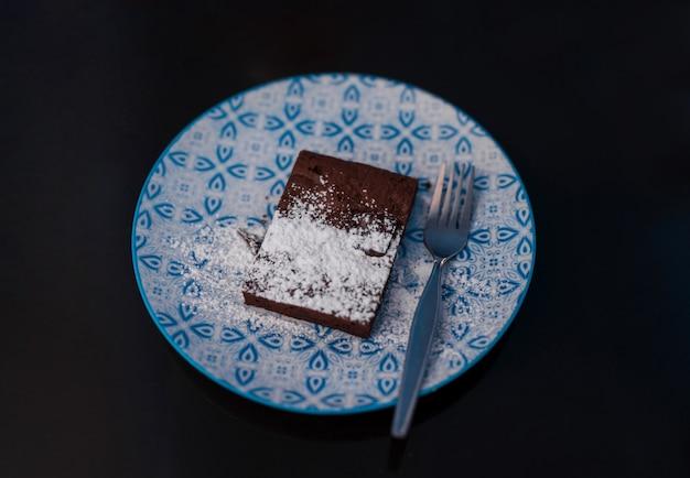 Foco seletivo brownie de formato quadrado de chocolate amargo com cobertura de açúcar de confeiteiro na mesa preta, assados caseiros