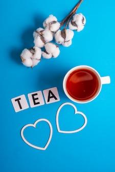 Foco seletivo: chá preto do ceilão em uma caneca branca sobre um fundo de papel comum azul. copyspace. letras de papelão dispostas na palavra tea em inglês
