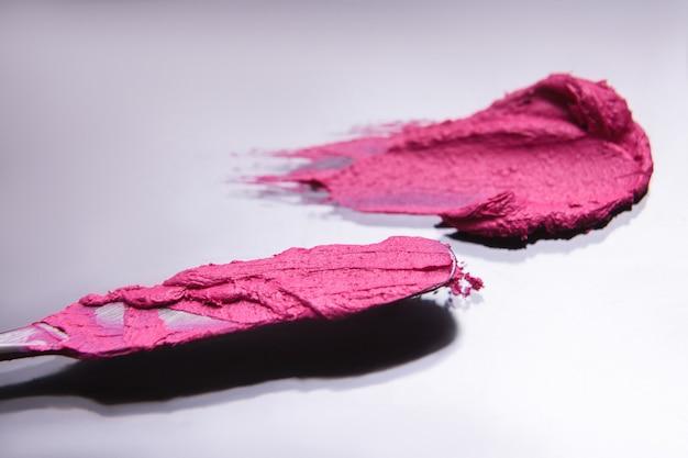 Foco seletivo da ferramenta cosmética do batom rosa derrame. processo de maquiagem criativa, fundo de estilo bonito. revista glamorosa, conceito de beleza