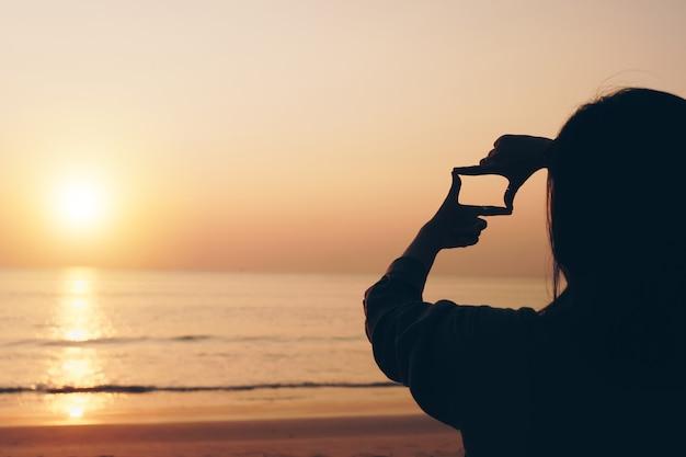 Foco seletivo das mãos da mulher fazendo um quadro com um gesto do dedo com o nascer do sol na montanha