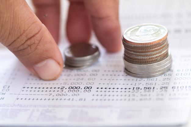 Foco seletivo das moedas do tailandês empilhadas sobre a página do extrato da conta bancária.