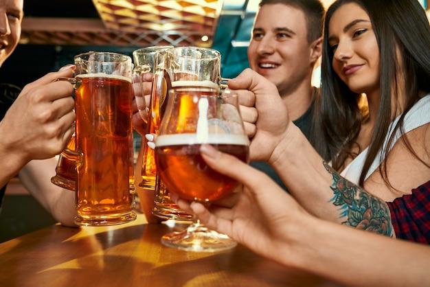 Foco seletivo de canecas de cerveja nas mãos de jovens amigos felizes no pub. companhia alegre descansando juntos nos fins de semana e bebendo cerveja no bar. conceito de felicidade e bebida.