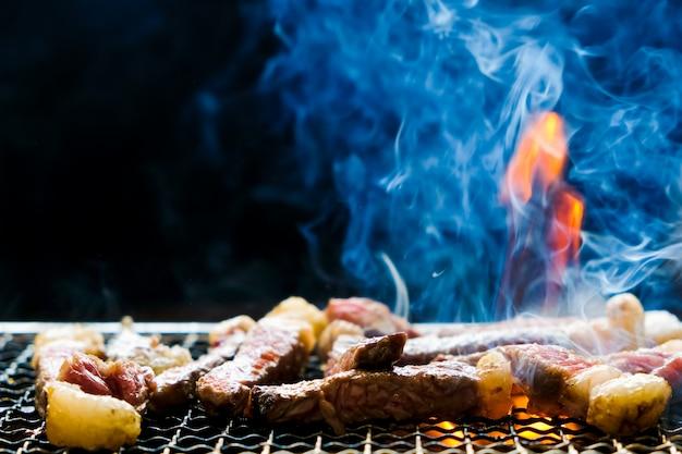Foco seletivo de churrasco de bife suculento fatiado carne grelhando no fogão de carvão de rack com chama de fumaça e fogo em fundo preto.