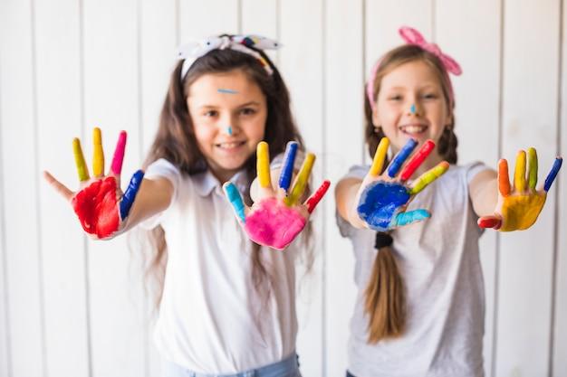 Foco seletivo de duas meninas sorridentes mostrando as mãos de tinta colorida