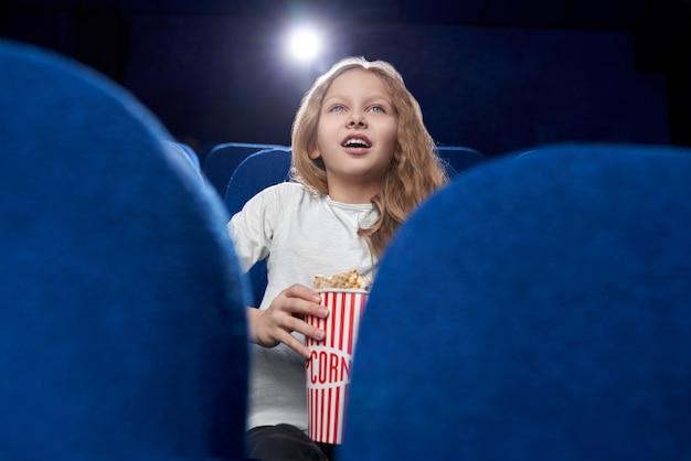 Foco seletivo de loira animada assistindo filme no cinema