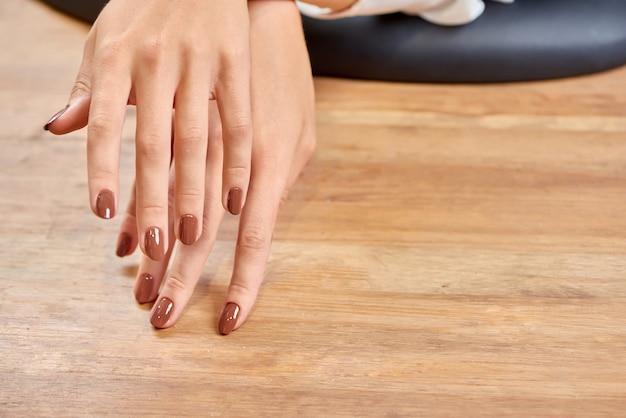 Foco seletivo de mãos femininas com maravilhosa manicure marrom.
