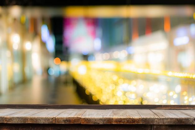 Foco seletivo de mesa de madeira na frente de luzes de seqüência de caracteres decorativas indoor