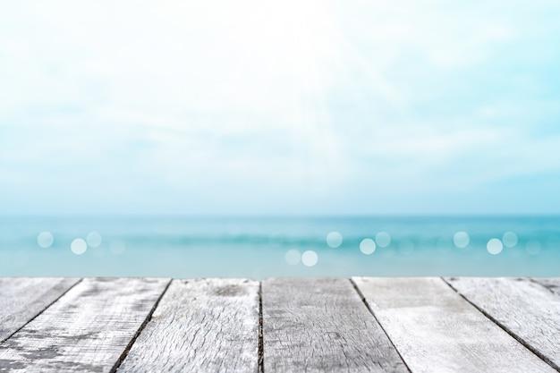 Foco seletivo de mesa de madeira velha com fundo de praia bonito para exibir seu produto.