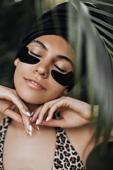 Foco seletivo de mulher com tapa-olhos. vista frontal de uma mulher atraente sob uma árvore exótica.