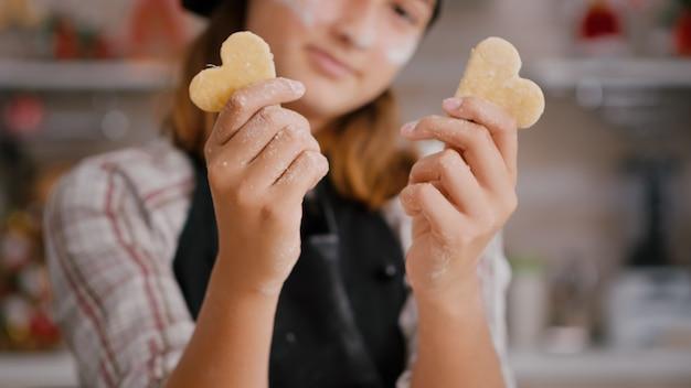 Foco seletivo de neto segurando massa de biscoito com formato de coração nas mãos