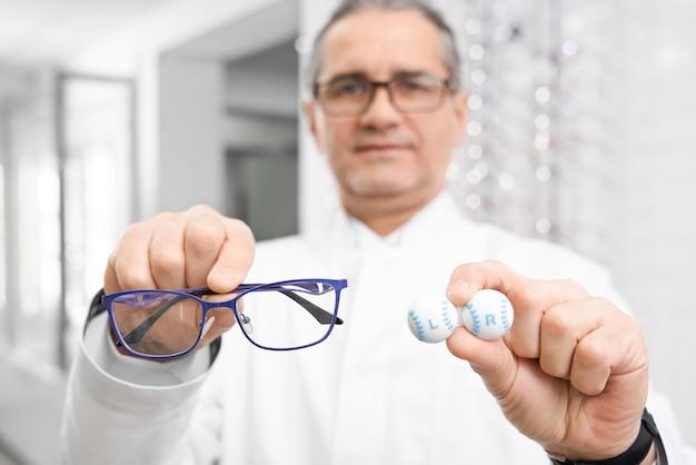 Foco seletivo de óculos e lentes nas mãos do oculista masculino