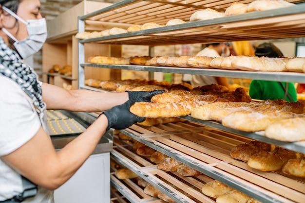 Foco seletivo de padeiros latinos colocando pães recém-assados nas prateleiras com máscara protetora