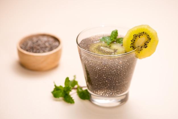 Foco seletivo de sementes de chia bebida com água em vidro transparente com erva-cidreira.
