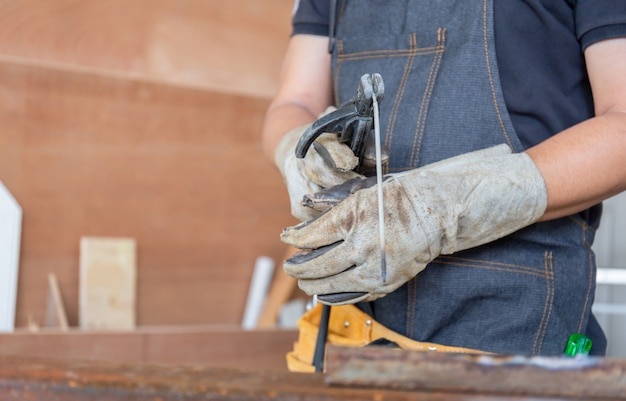 Foco seletivo de suportes de eletrodo de solda com fio de solda na mão do trabalhador, conceito de artesão