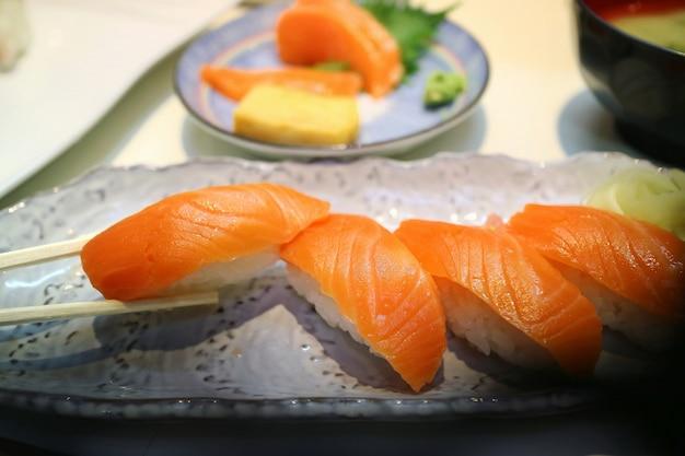 Foco seletivo de sushi nigiri de salmão com pauzinhos. famosa comida japonesa. conceito de comida.