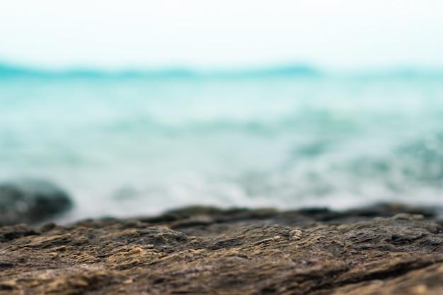 Foco seletivo de textura de pedra preta para mostrar produto com fundo de praia.