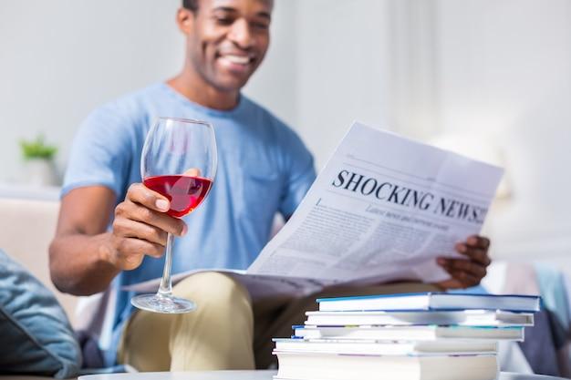 Foco seletivo de um copo com vinho tinto nas mãos de um homem alegre e positivo enquanto lê um jornal