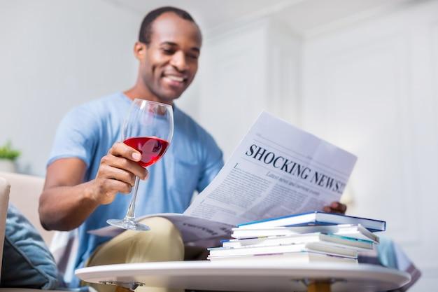 Foco seletivo de um copo sendo enchido com vinho tinto nas mãos de um homem relaxado e positivo
