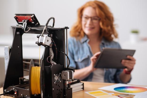 Foco seletivo de um filamento sendo colocado na impressora 3d e sendo usado para impressão
