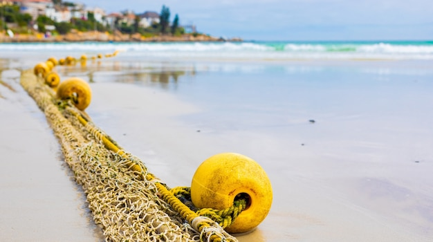Foco seletivo de um flutuador de uma rede de pesca tradicional em uma praia arenosa