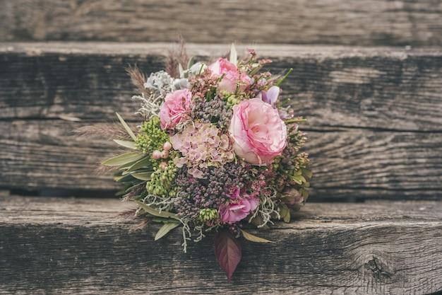 Foco seletivo de um lindo buquê de flores pequenas em uma superfície de madeira