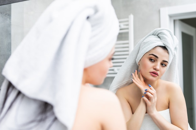 Foco seletivo de uma bela jovem sorridente tocando o rosto enquanto olha para o espelho