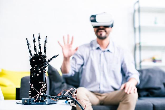 Foco seletivo de uma mão robótica com um homem alegre sentado ao fundo e testando-o