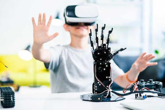 Foco seletivo de uma mão robótica na mesa com um garotinho sorridente testando óculos de realidade virtual ao fundo