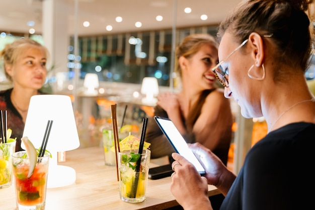 Foco seletivo de uma menina de óculos usando o telefone móvel, sentado em uma mesa em um restaurante com outras mulheres bebendo cocktails