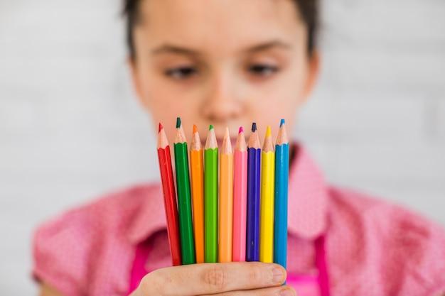 Foco seletivo de uma menina olhando para lápis coloridos na mão