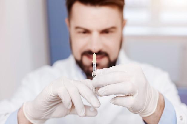 Foco seletivo de uma seringa sendo segurada por um médico profissional de boa aparência enquanto aplica uma injeção