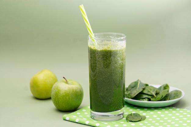 Foco seletivo de vidro misturado do batido verde, fundo verde. comida saudável.