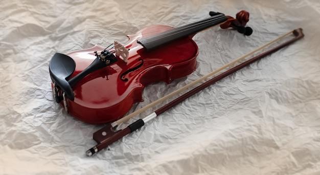 Foco seletivo de violino de madeira colocar ao lado do arco
