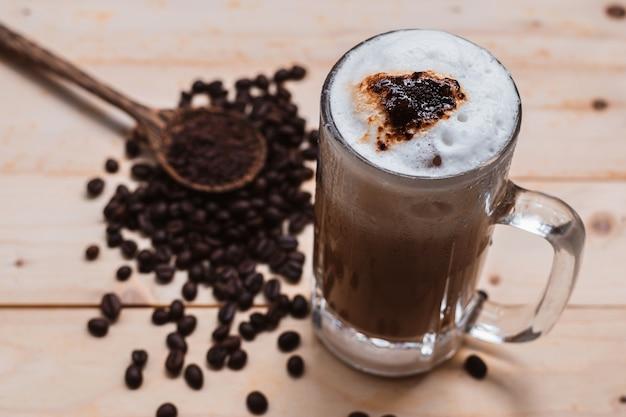 Foco seletivo de vista superior de espuma de café gelada em copo de caneca de café no piso de madeira.
