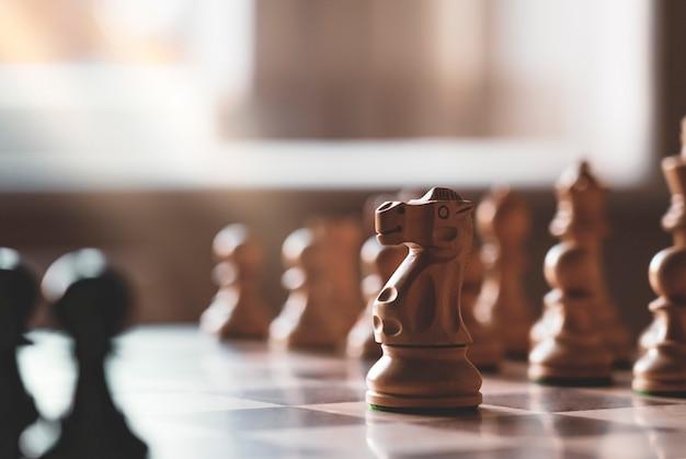 Foco seletivo de xadrez de madeira cavaleiro no jogo de tabuleiro com fundo desfocado,